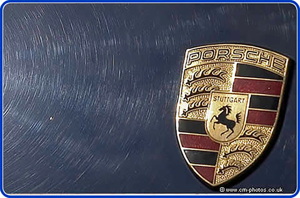 Porsche Badge on dirty car.